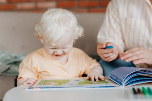 A Child Happily Looking at a Coloring Book
