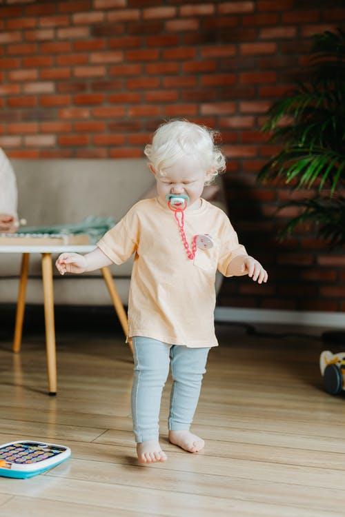 A Toddler Walking with a Pacifier in her Mouth