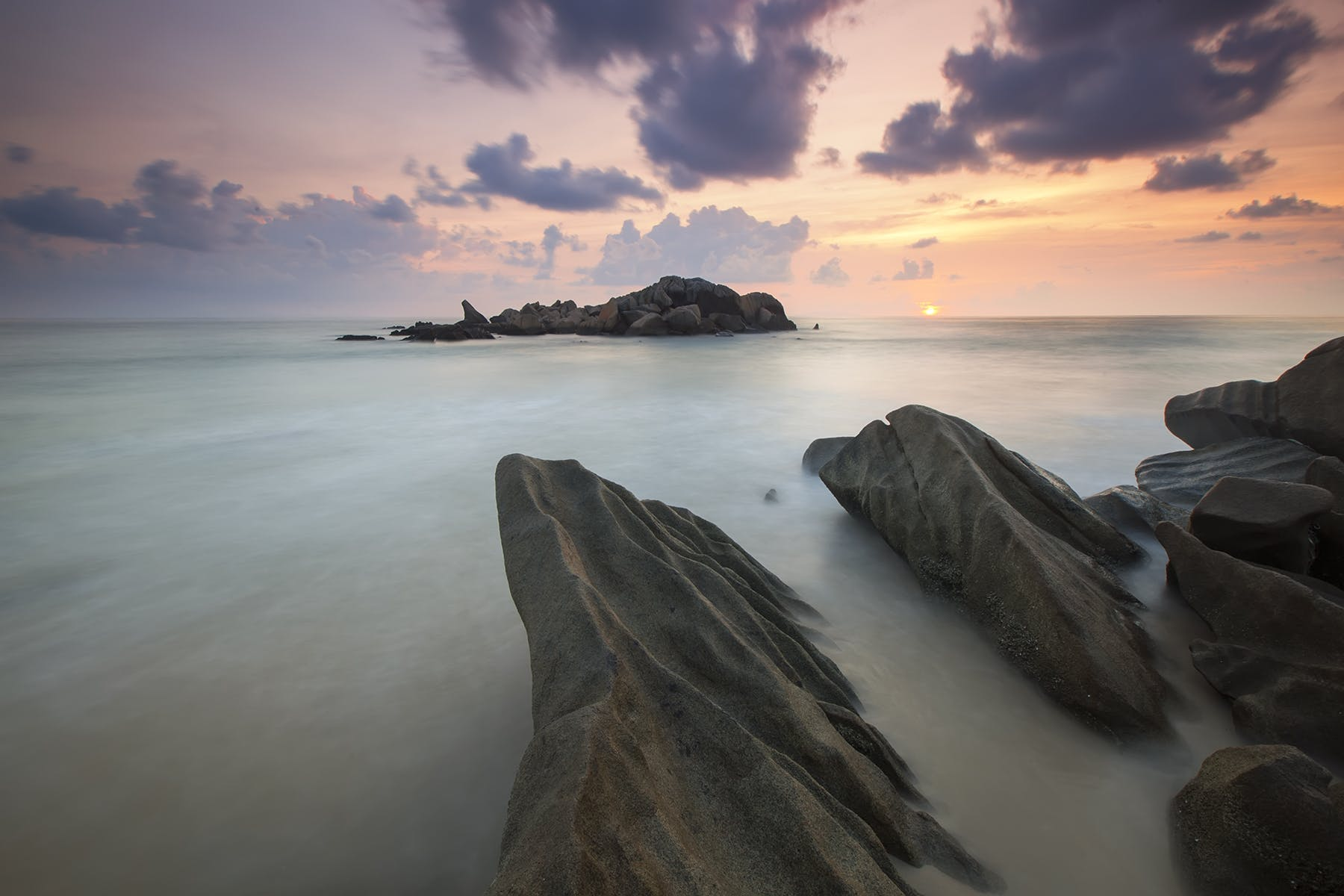 Rock Near a White Foggy Area Under an Orange Sky