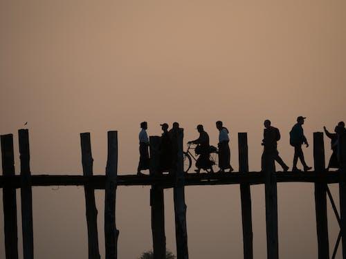 Silhouette of People Walking on Wooden Bridge