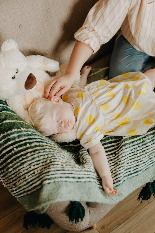 Adult Hand Touching Baby Sleeping on Sofa