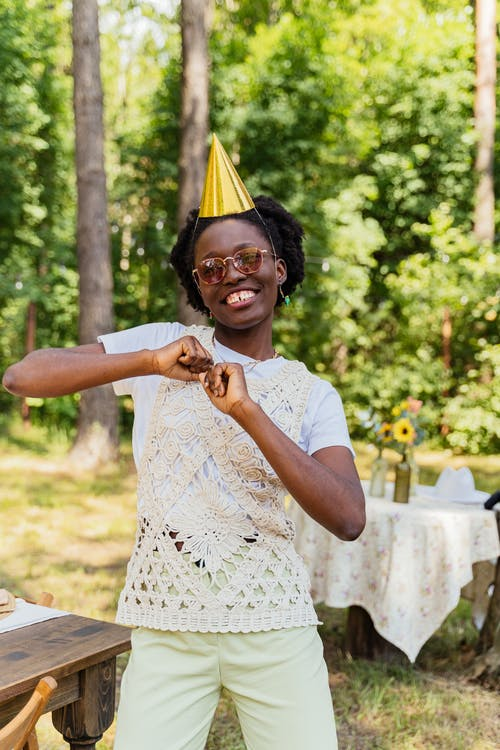 Woman Dancing while Wearing a Gold Party Hat