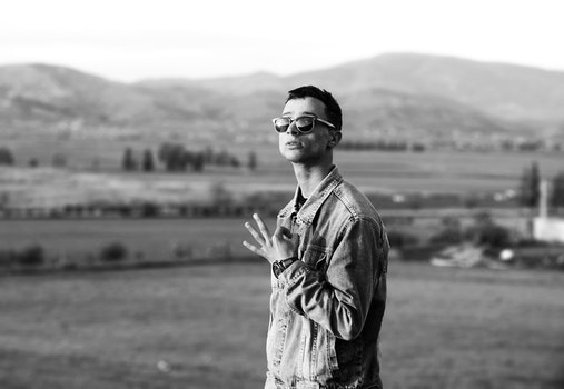 Grayscale Photo of Man Wearing Denim Jacket Near Mountain at Daytime