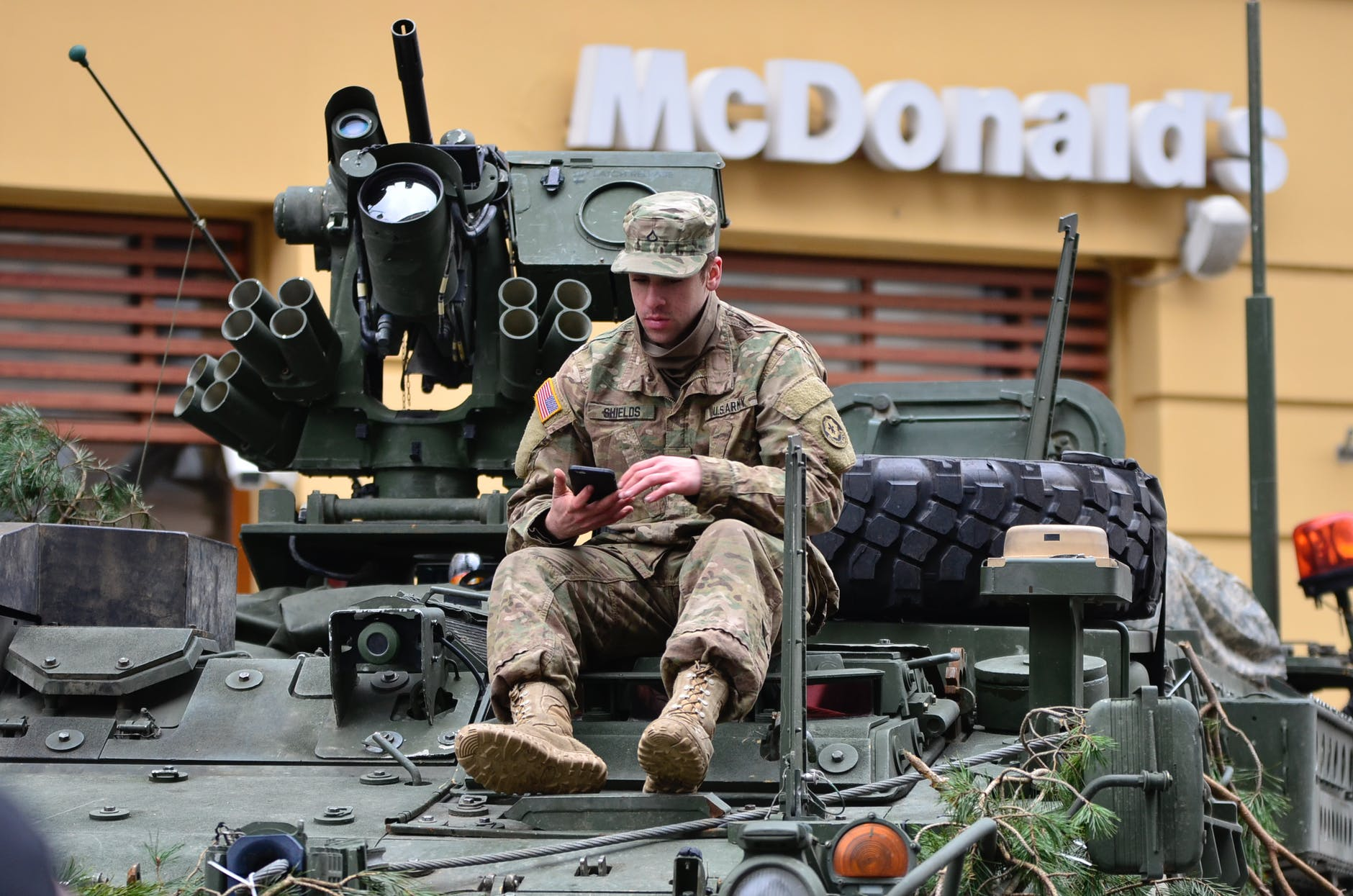 military man sitting in the tank in front of McDonald's