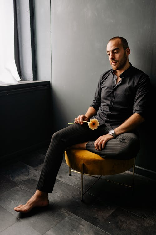 https://www.pexels.com/photo/man-in-black-dress-shirt-sitting-on-yellow-chair-by-the-window-8911445/