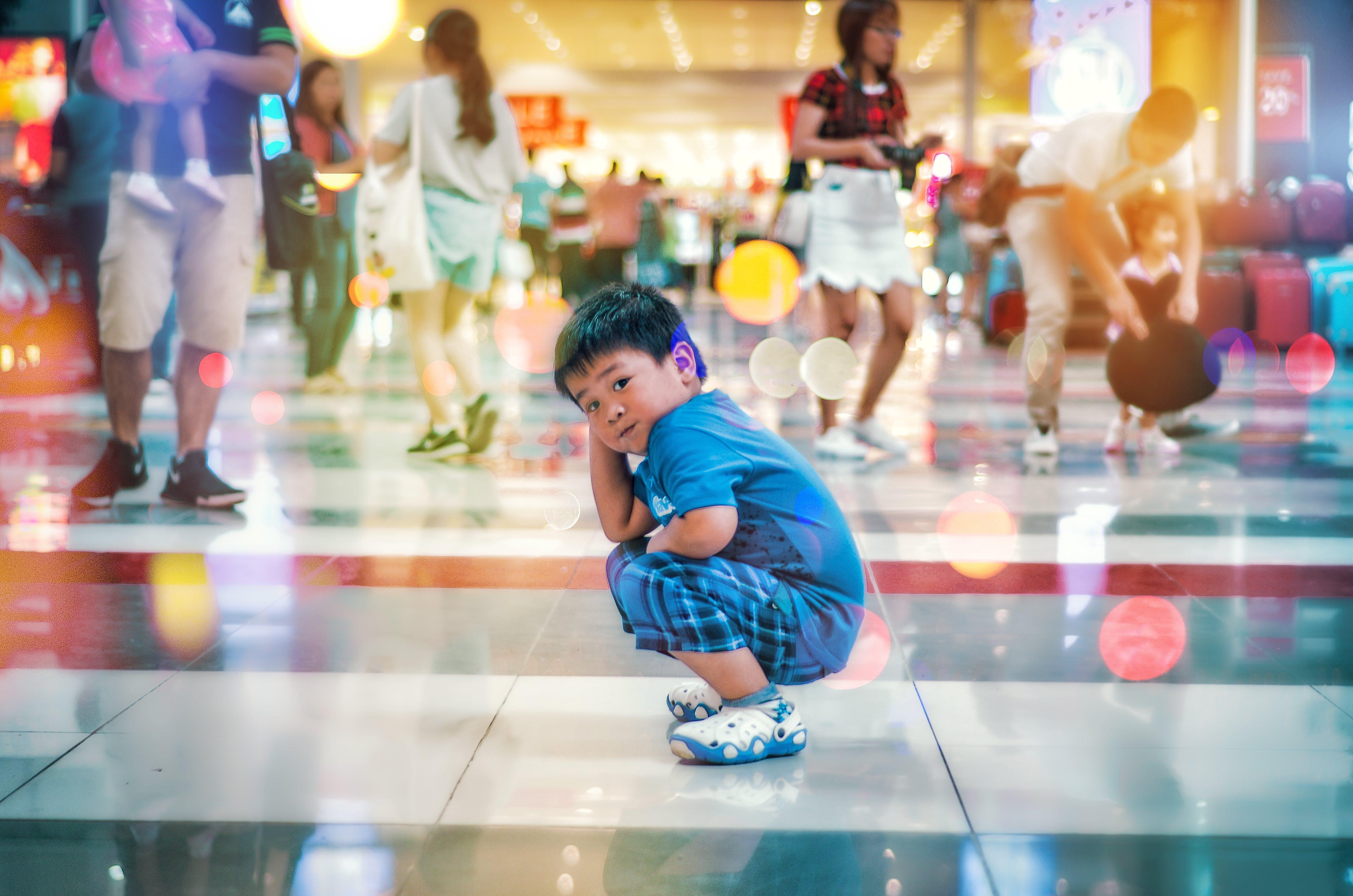 Boy Squating on White Floor Tile