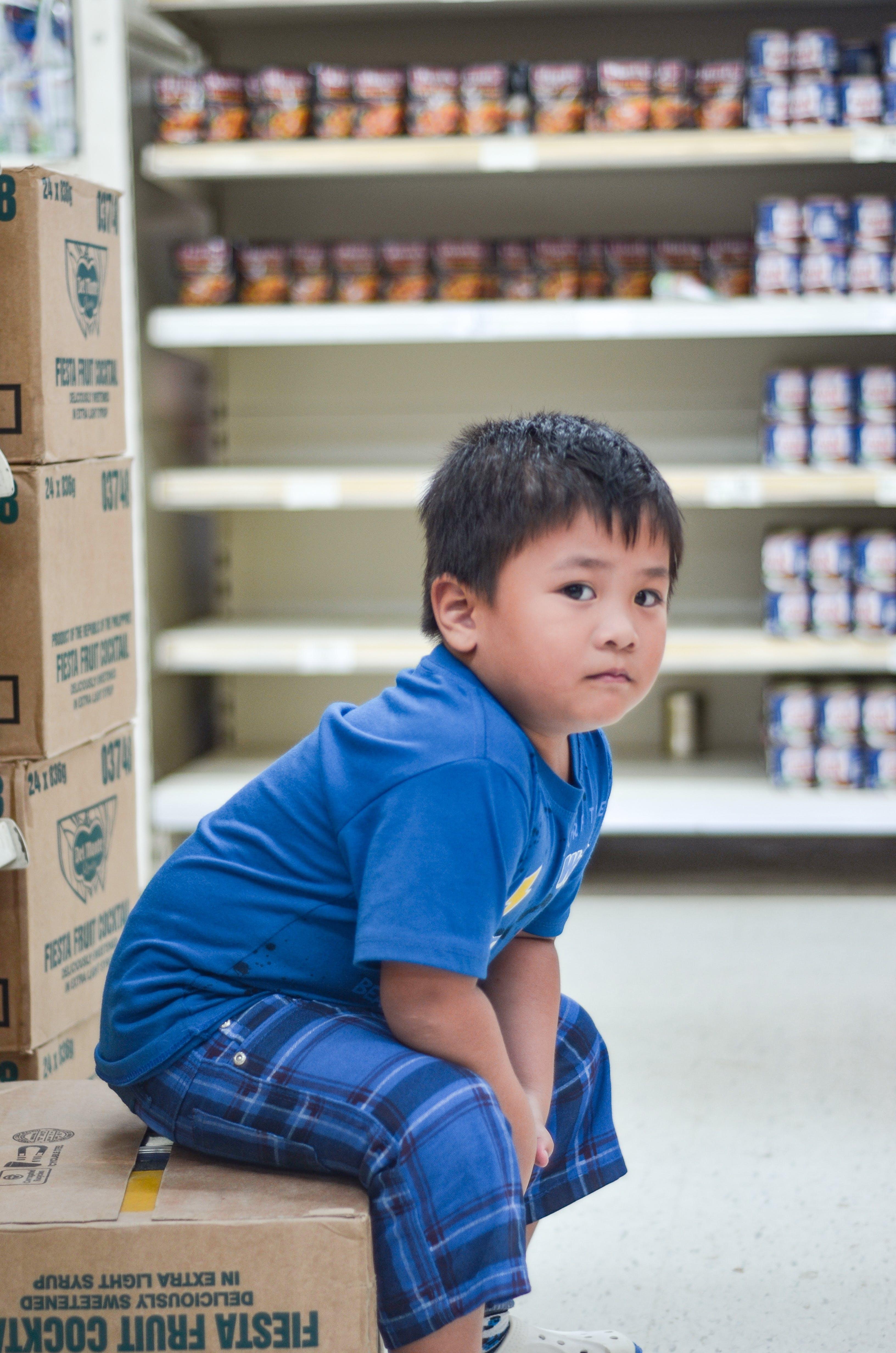 Boy Wearing Blue Crew-neck T-shirt Sitting on Cardboard Box