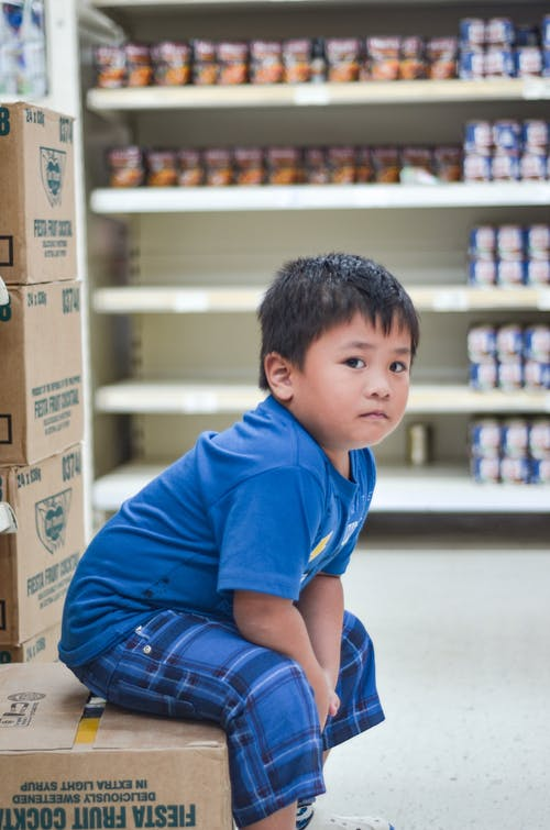 Boy Wearing Blue Crew-neck T-shirt Sitting on Cardboard Box
