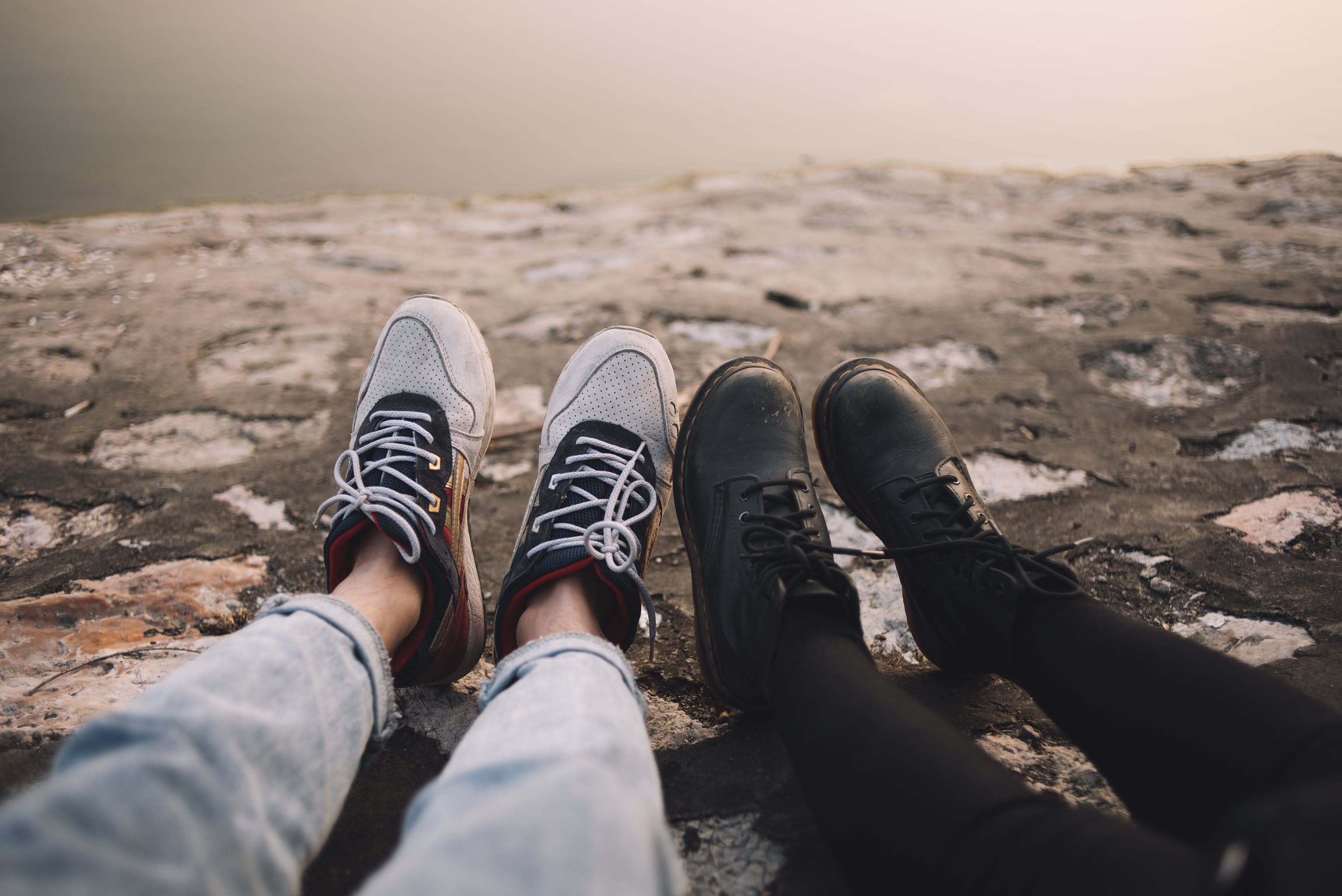 Two Person Wearing Pants and Shoes Sits on Ground at Daytime