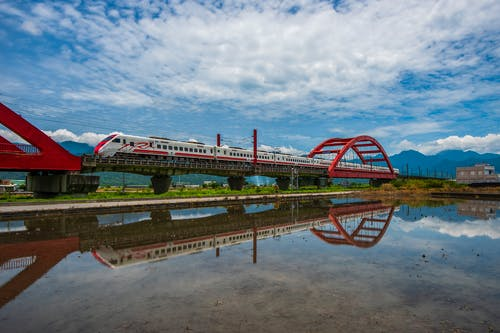 Red and White Wooden Bridge over River Under Blue Sky