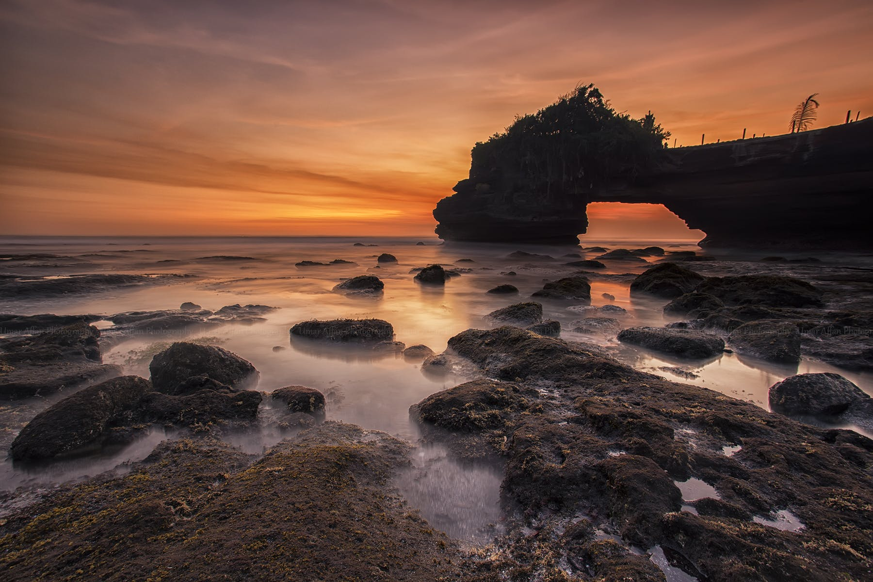 Orange and Yellow Sunset Skies over Grey Seashore Rocks and Calmed Ocean