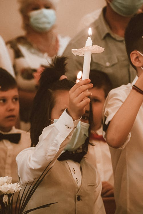 A Boy in White Dress Shirt With Face Mask Holding a Lighted Candle