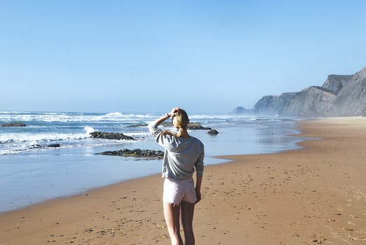 Woman in Gray Long-sleeved Shirt With Pink Short Shorts Standing Near Sea