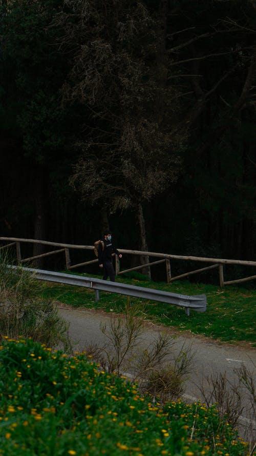 Woman in Black Jacket and Black Pants Sitting on Gray Metal Railings