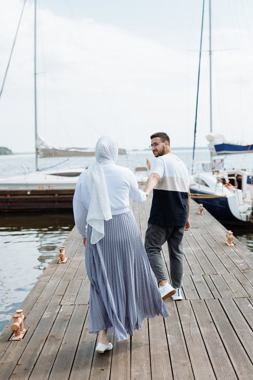 A Couple Waling on a Wooden Dock