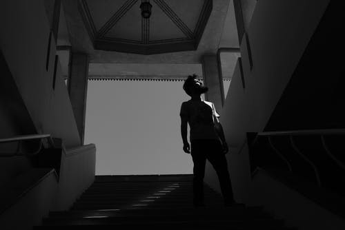 A Grayscale of a Bearded Man Standing on Stairs