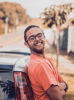 Man in Orange T-shirt Leaning on a Car