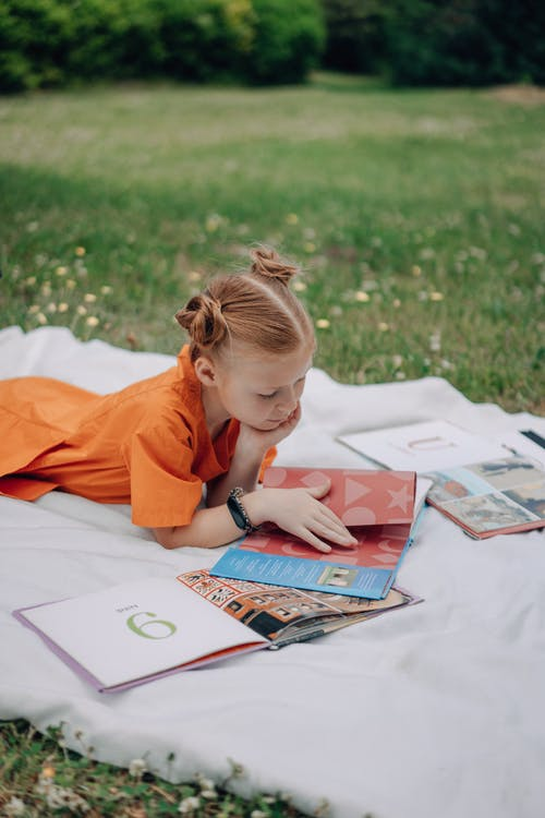 A Girl Reading Books Outdoors