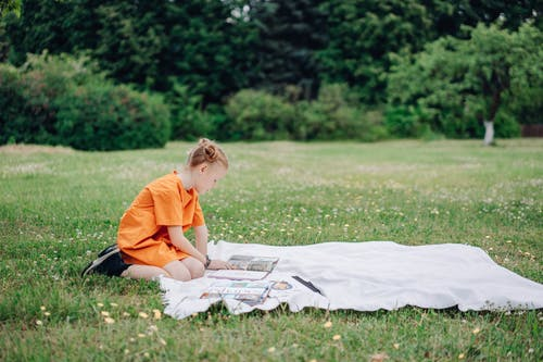 A Girl Reading Books on a Blanket Outdoors