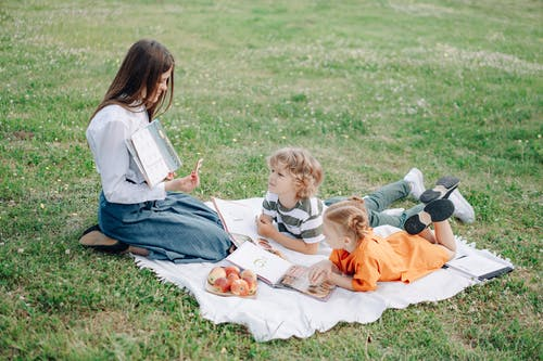 A Woman Teaching Children while on a Blanket Outdoors