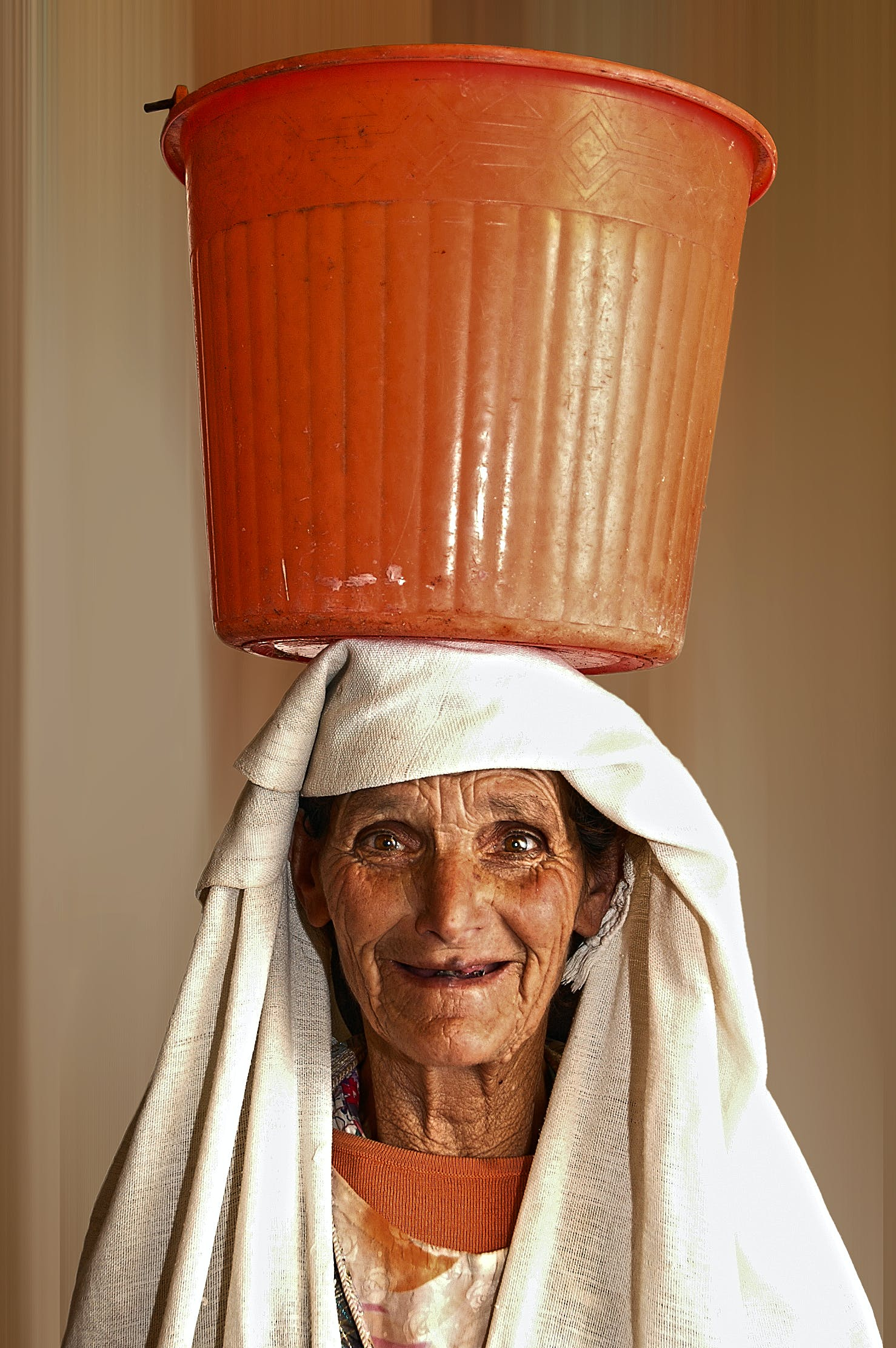 Portrait Photo of Woman Carrying Orange Plastic Pail on Head