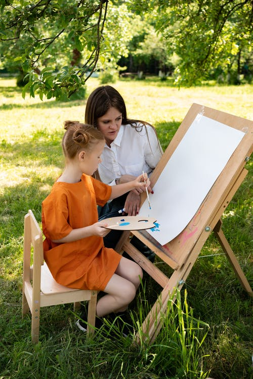 A Woman Teaching a Girl How to Paint