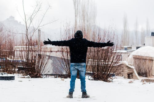 Person Wears Black Jacket and Blue Denim Jeans Standing on Snow Covered Field