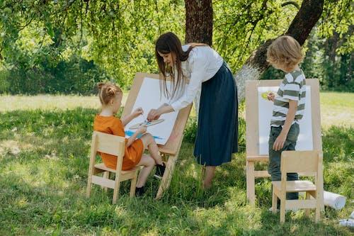Een Vrouw En Kinderen Die Buiten Schilderen