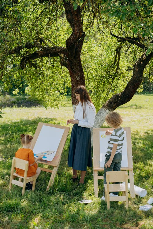A Woman and Kids Painting Outdoors