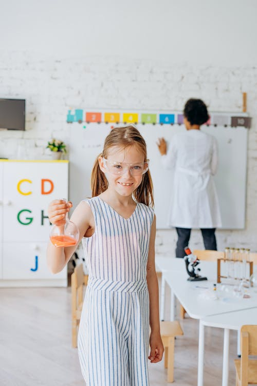 Girl With Safety Glasses Holding A Glass Beaker