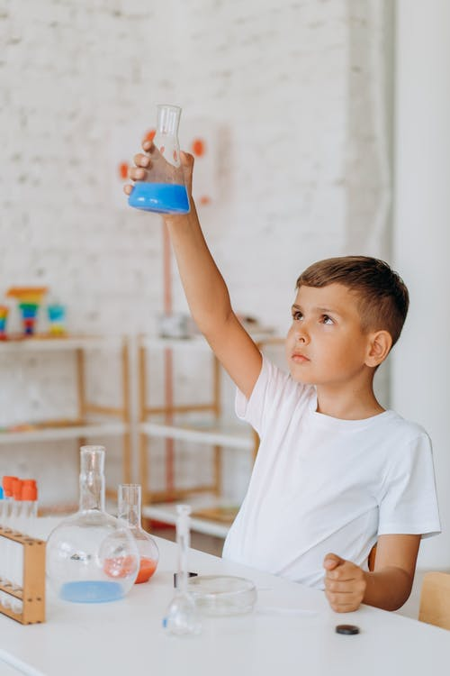Boy Looking At A Beaker With Blue Substance