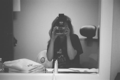 Grayscale Photo of Person Taking Photo of Herself In Front Of A Mirror