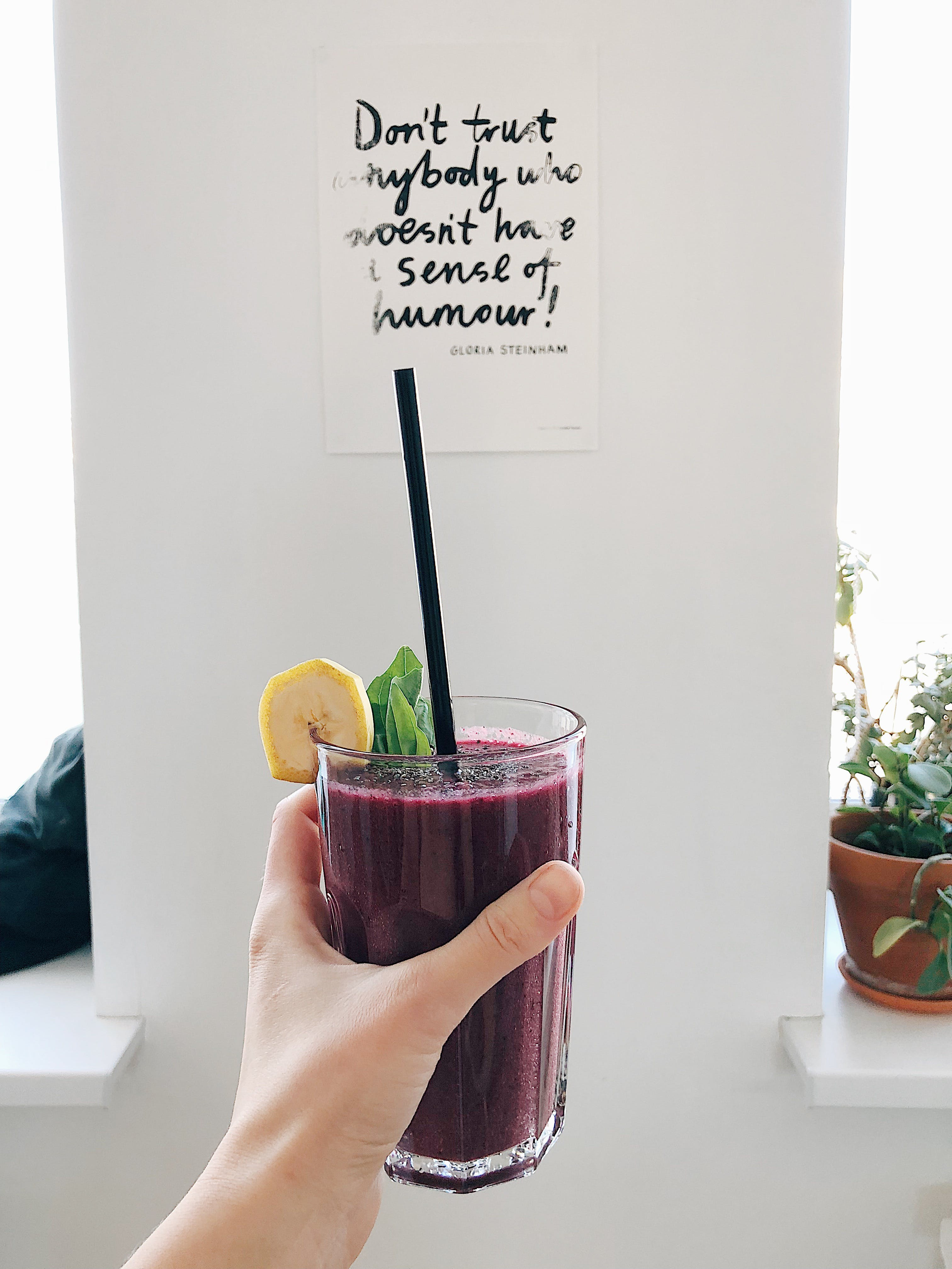 Person Holding Clear Drinking Glass With Purple Smoothie With Quotation Decor