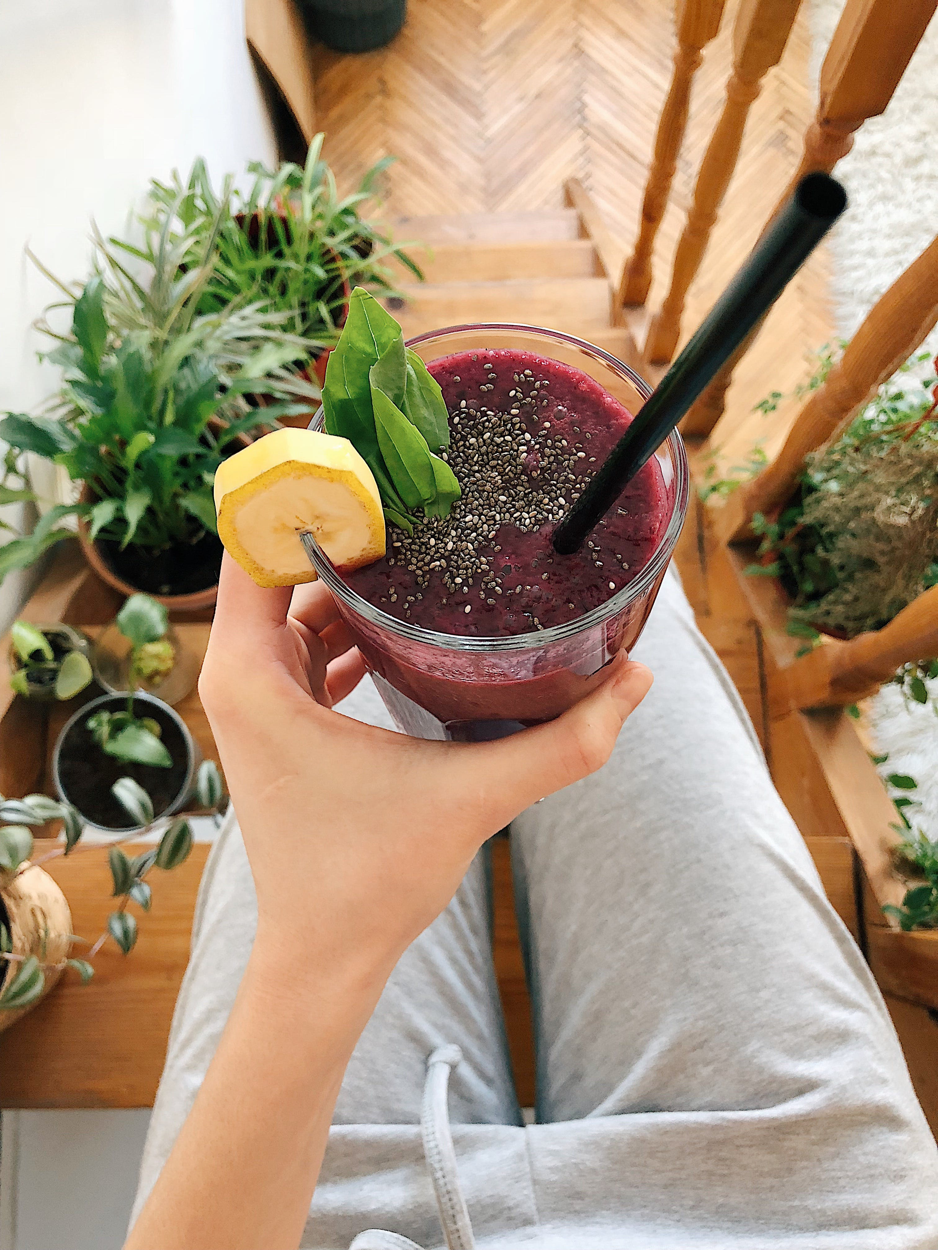 Person's Hand Holding Drinking Glass Filled With Smoothie