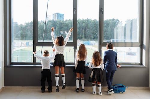 4 Children Standing Near Glass Window
