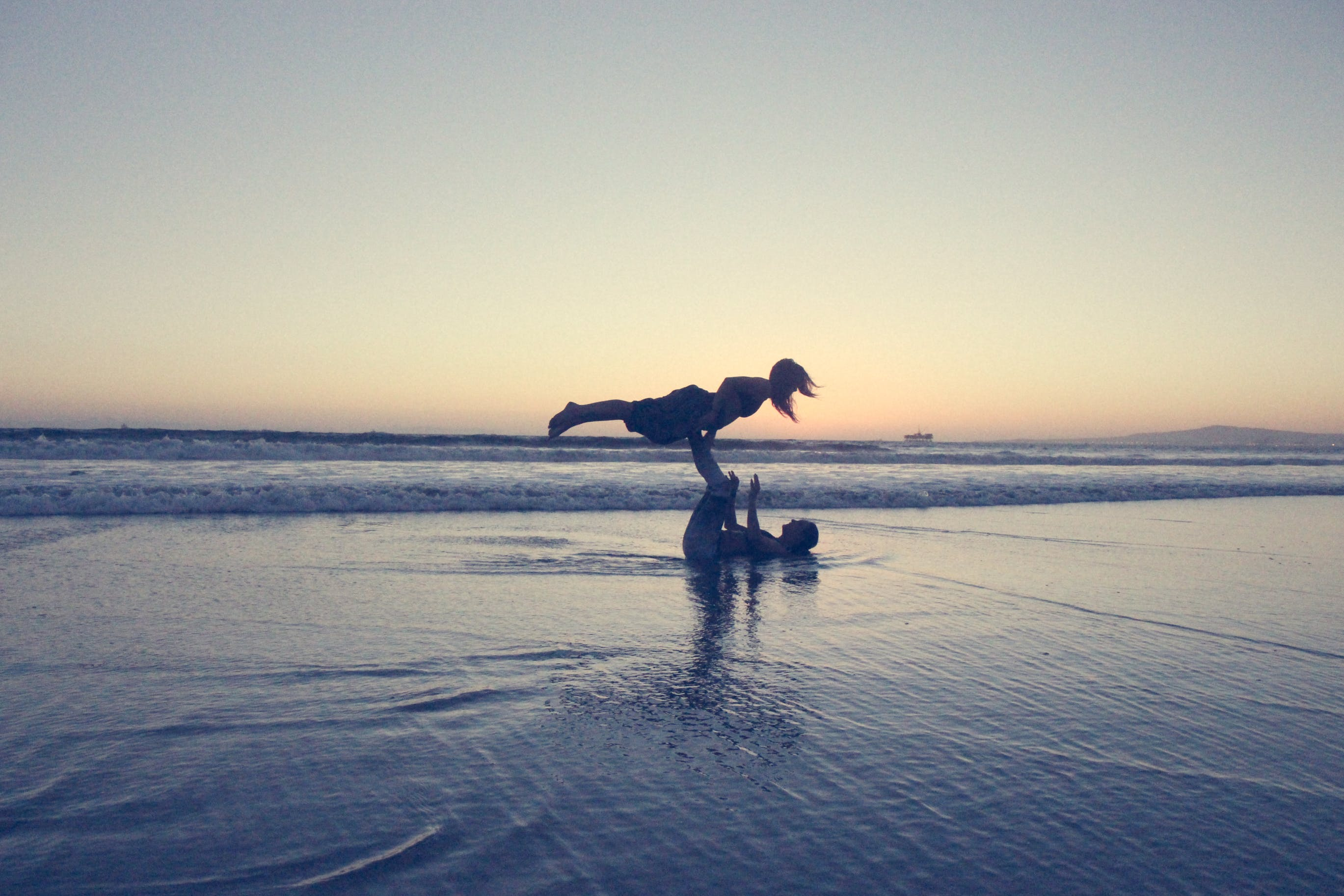 Landscape Photography of Man Lifting Woman by His Foot on Seashore