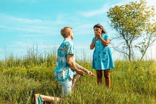 Boy and Girl Standing on Green Grass Field