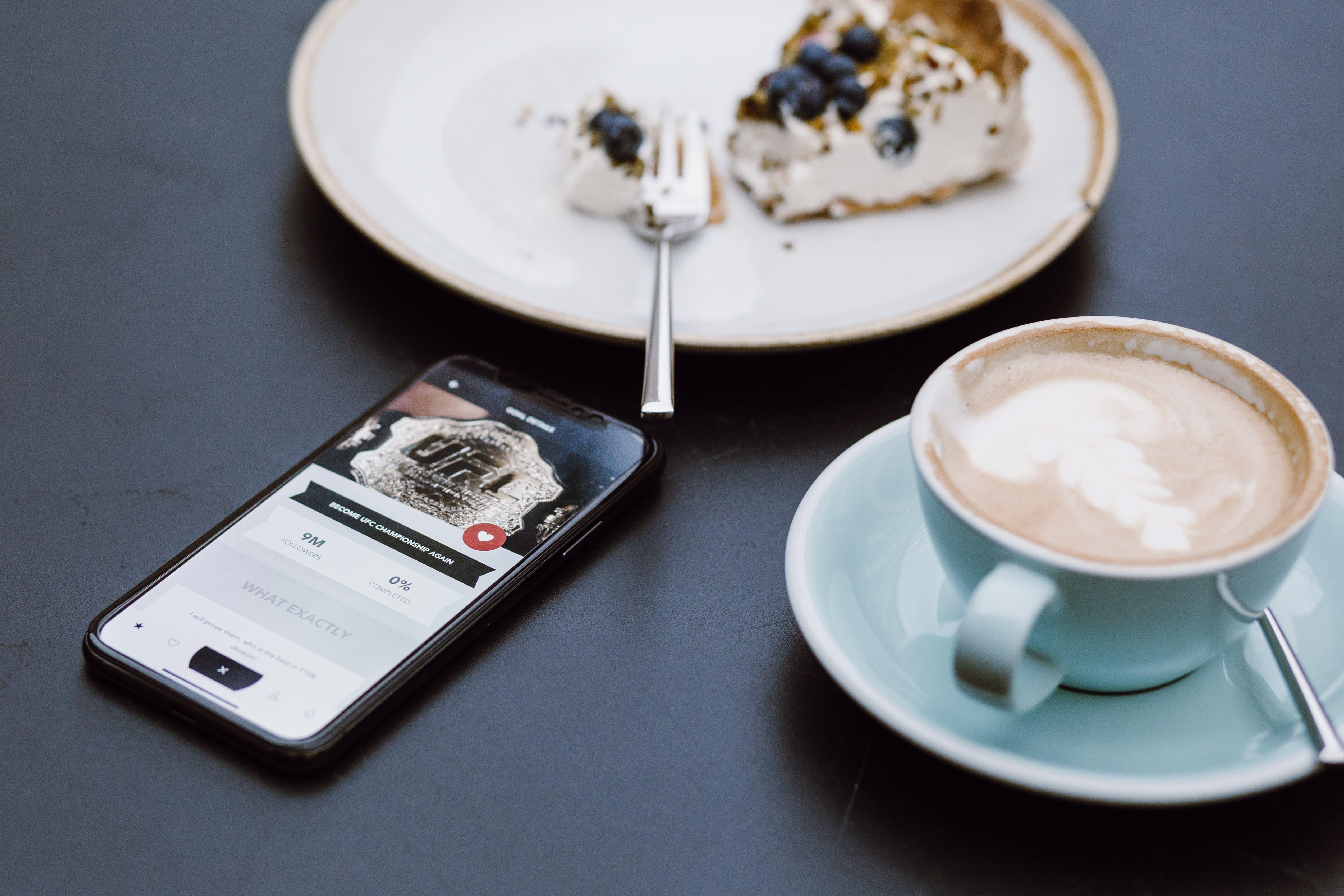 Black Smartphone Beside Coffee Mug in Shallow Focus Lens