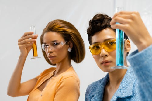 Women Holding Graduated Cylinders