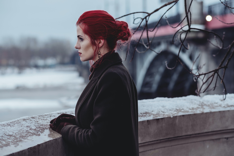 Woman Wearing Black Coat Standing In-front of Balcony