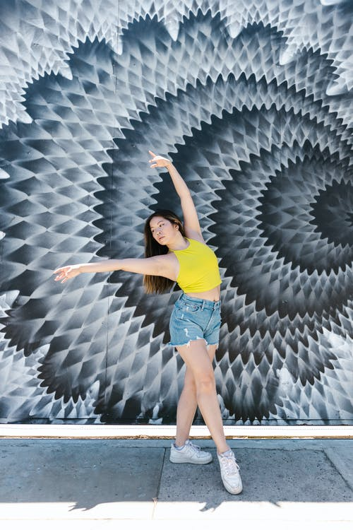 Woman in Yellow Tank Top and Blue Denim Shorts Dancing