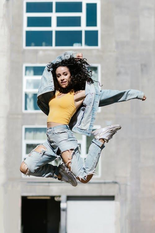 A Woman in Denim Clothes Jumps Near the Concrete Building