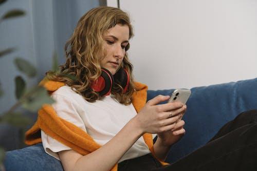 Gratis lagerfoto af indendørs, kvinde, mobiltelefon