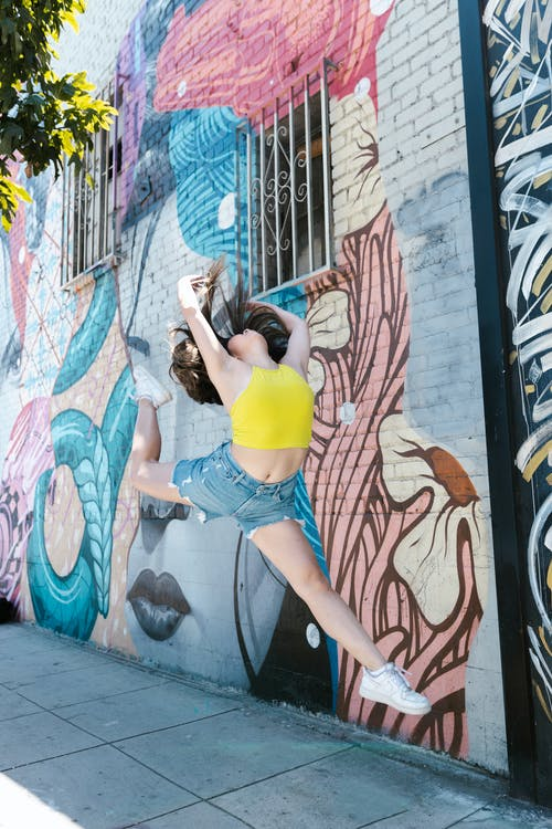 Woman in Yellow Crop Top Jumping near Graffiti Wall