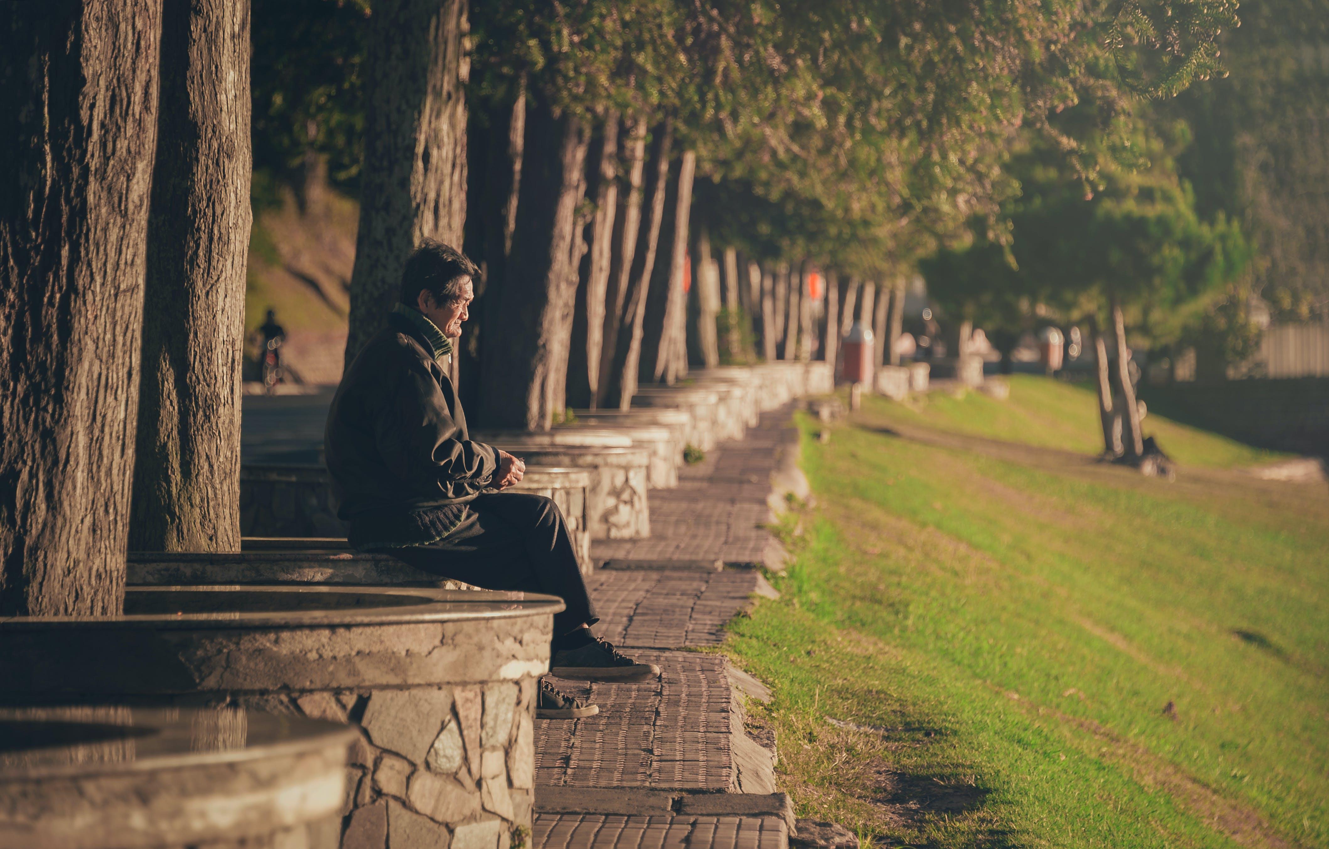 Man Seating on Concrete Base