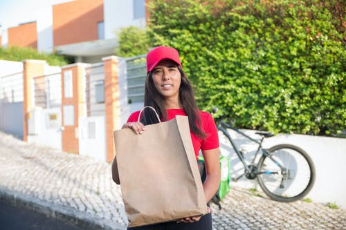 Woman in Red Cap and Red Shirt Holding Brown Paper Bag