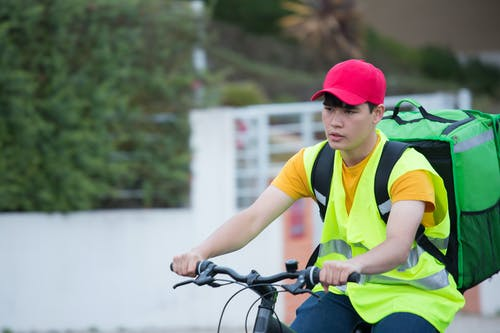 Man in Yellow Shirt and Red Cap Riding a Bike