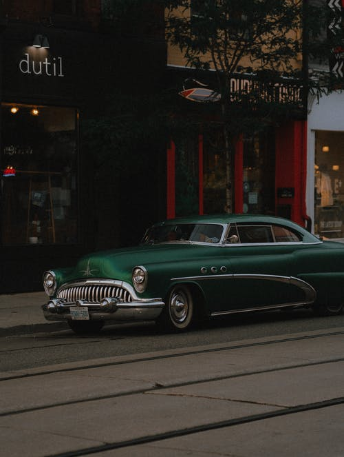 Green Classic Car Parked Beside Store