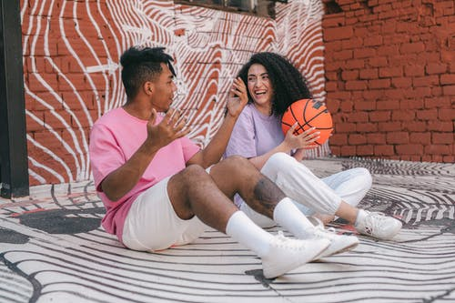 Man in White T-shirt and White Pants Sitting Beside Woman Holding a Basketball