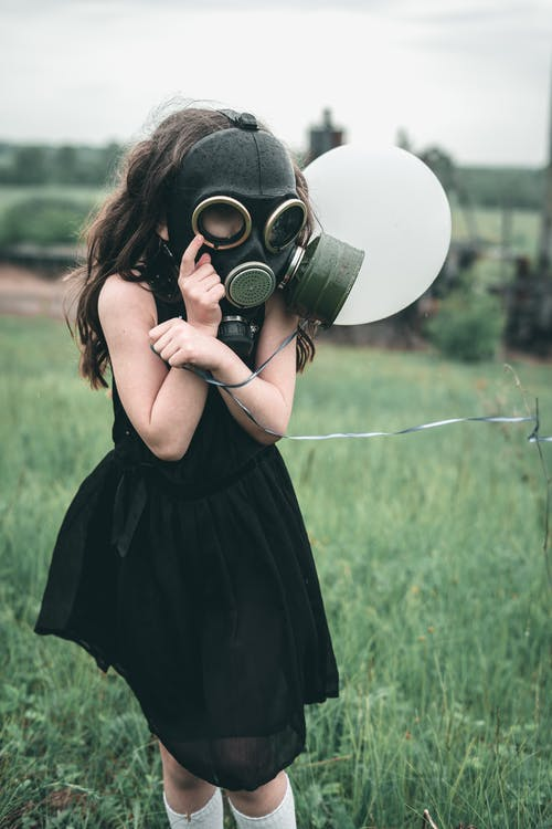 Young Girl in Black Dress wearing Gas Mask